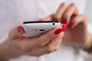 Frau mit schönen Fingernäglen schreiubt eine Nachricht