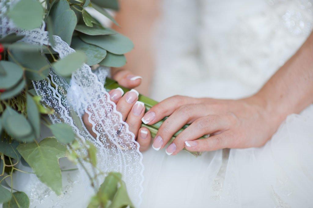 Schöne Hochzeitsnägel für die Fotos mit dem Brautstrauß